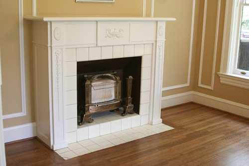 Beautiful wood fireplace with a mantle and ceramic tile.